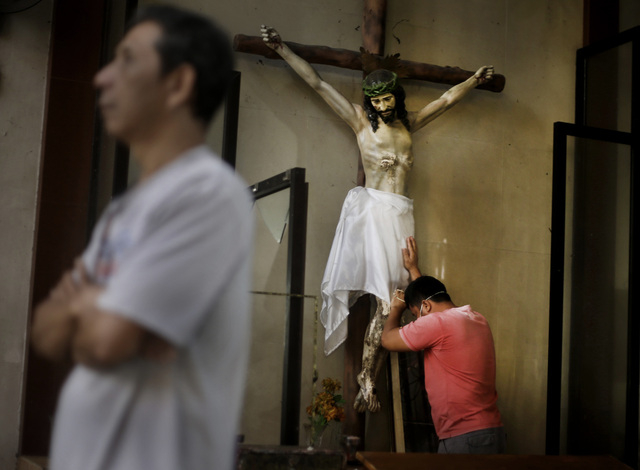 A Filipino man prays on a statue of Jesus Christ prior to a Mass at Santo Nino church that was damaged by Typhoon Haiyan in Tacloban, Philippines, Sunday, Nov. 17, 2013. Typhoon Haiyan, one of the ...