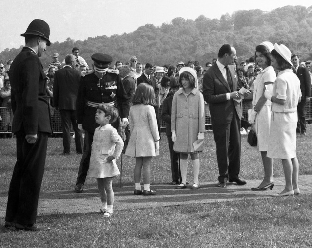 In this May 14, 1965 file photo, John Kennedy Jr., son of U.S. President John F. Kennedy, talks with a British police officer after the dedication ceremony for the memorial to the late president a ...