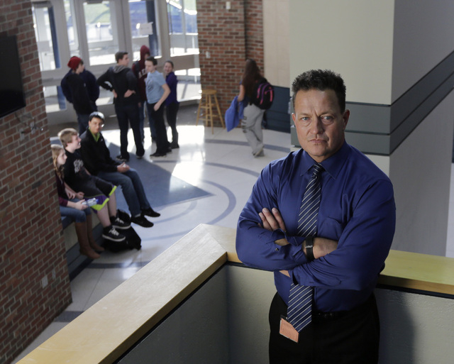 Columbia High School Principal John Sawchuk poses at the school on Thursday, Nov. 14, 2013, in East Greenbush, N.Y. In 2004 Sawchuk found himself wrestling a 16-year-old student for the loaded sho ...