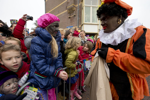 "Children, some with faces painted black, wait  for ""Zwarte Piet"" or ""Black Pete"", right, to hand them candy after they arrived with Sinterklaas, or Saint Nicholas, in Hoorn, no ..."
