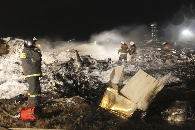In this photo provided by Russian Emergency Situations Ministry fire fighters and rescuers work at the crash site of a Russian passenger airliner near Kazan, the capital of the Tatarstan republic, ...
