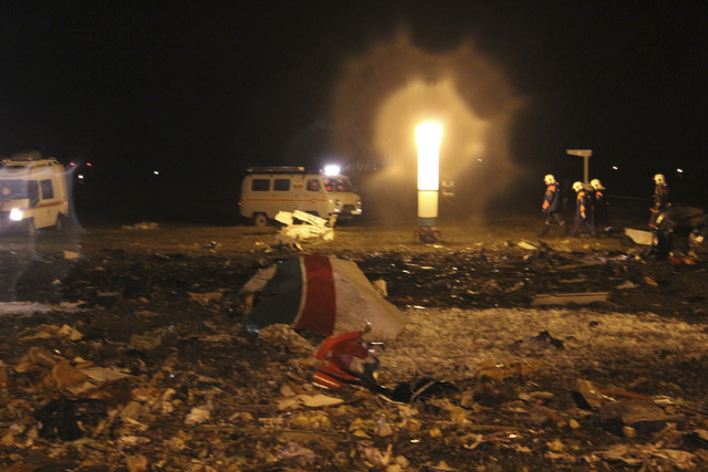 In this photo taken on Sunday, Nov. 17, 2013 and provided by Russian Emergency Situations Ministry, fire fighters and rescuers work at the crash site of a Russian passenger airliner near Kazan, th ...