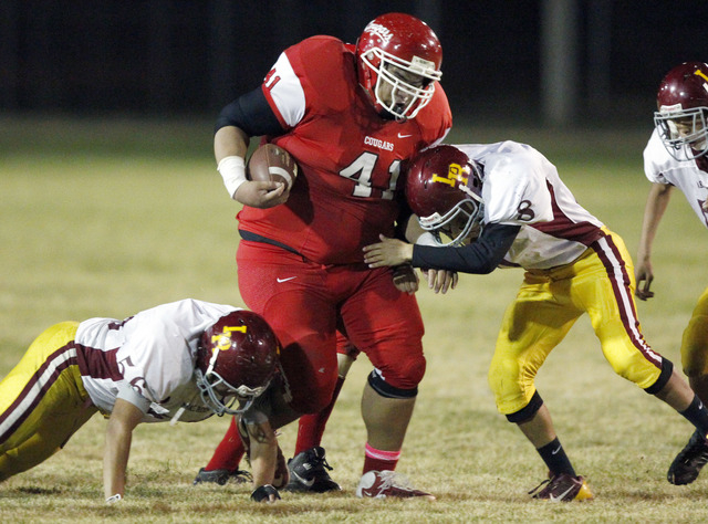 In this Nov. 1, 2013 photo, Lake Roosevelt's High School's Trey Nicholson, left, and Nathaniel Hall try to tackle White Swan High School's Tony Picard, center, during a football game in White Swan ...