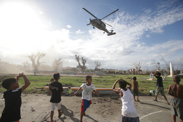Typhoon survivors watch as a US helicopter lands to deliver relief goods in Tanauan, Leyte province, central Philippines Wednesday Nov. 20, 2013. More than 4 million people have been displaced and ...