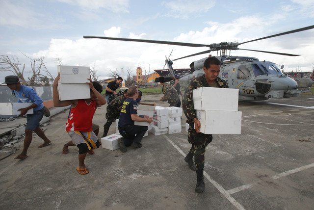 Typhoon survivors and Filipino soldiers bring relief goods brought down from a US helicopter as relief operations continue in Tanauan, Leyte province, central Philippines Wednesday Nov. 20, 2013.  ...