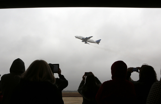 Students and instructors at the National Center for Aviation Training take pictures of Boeing 747 Dreamlifter from a hangar as it takes off Thursday, the day after it mistakenly landed at Col. Jam ...