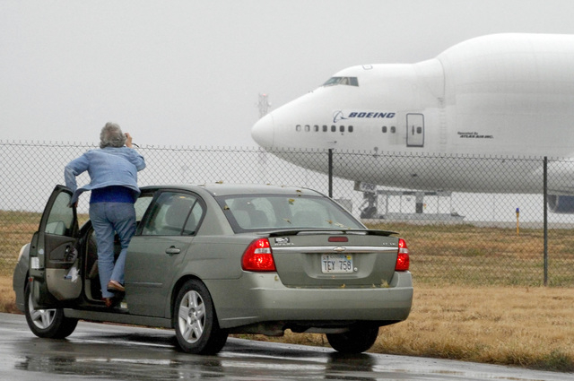 A woman tries to take a photo of a Boeing 747 Dreamlifter Thursday, Nov. 21, 2013, that mistakenly landed at Col. James Jabara Airport in Wichita, Kan. The jet landed Wednesday evening at the airp ...