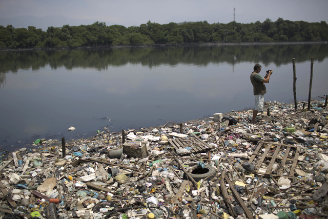 In this Oct. 23, 2013 photo, biologist Mario Moscatelli takes photographs from trash floating on the polluted waters of the Canal do Fundao in Rio de Janeiro, Brazil. Moscatelli, who oversees the  ...