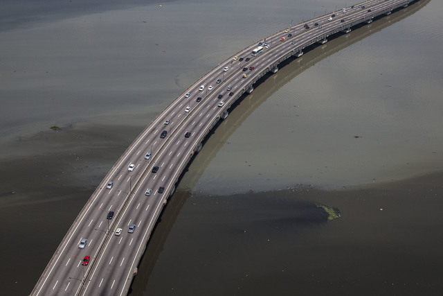 The polluted waters of Guanabara Bay float below a road leading to the international airport that serves Rio de Janeiro, Brazil, Tuesday, Nov. 19, 2013. Leonardo Gryner, chief operating officer of ...