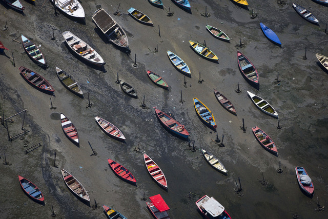 Small boats sit on the shore of Guanabara Bay in the suburb of Sao Goncalo, across the bay from Rio de Janeiro, Brazil, Tuesday, Nov. 19, 2013. The bay was home to a thriving artisanal fishing ind ...