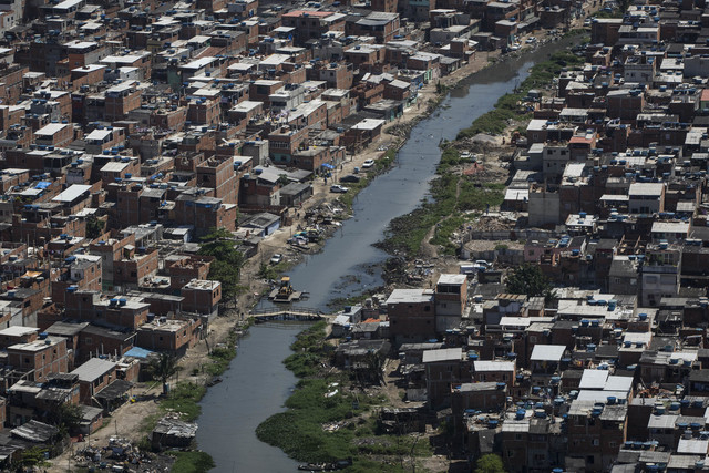 A polluted channel runs through the Rio das Pedras shantytown in Rio de Janeiro, Brazil, Tuesday, Nov. 19, 2013. Its not clear what consequences there might be if Rio doesnt clean up its waterways ...