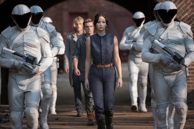This image released by Lionsgate shows Jennifer Lawrence as Katniss Everdeen, from foreground to background, Josh Hutcherson as Peeta Mellark and Woody Harrelson as Haymitch Abernathy in a scene f ...