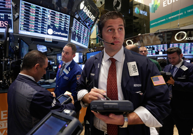 In this Tuesday, Nov. 19, 2013, file photo, Trader Thomas Donato, center, works on the floor of the New York Stock Exchange. Global stock markets, except Japan, were in the red Thursday Nov. 21, 2 ...