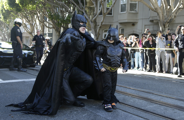 Miles Scott, dressed as Batkid, right, walks with Batman before saving a damsel in distress in San Francisco, Friday, Nov. 15, 2013. (AP Photo/Jeff Chiu)