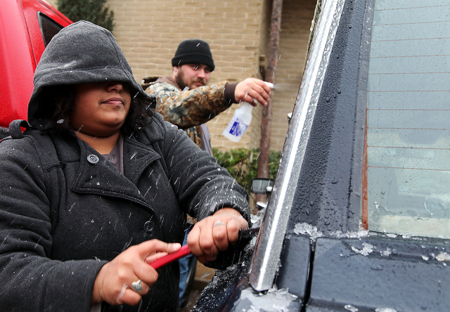 Samantha Hernandez scrapes ice off of the windows after Kenneth Fields sprays them with a concoction of vinegar and water to soften the ice on Saturday in Odessa, Texas. The fierce weather has cau ...