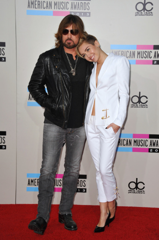 Billy Ray Cyrus, left, and Miley Cyrus arrive at the American Music Awards at the Nokia Theatre L.A. Live on Sunday, Nov. 24, 2013, in Los Angeles. (Photo by Jordan Strauss/Invision/AP)