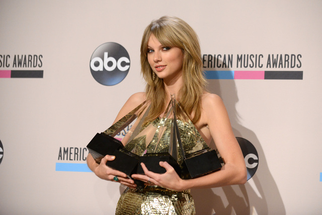 "Taylor Swift poses backstage with the awards for favorite album - country for ""Red"", favorite female artist - pop/rock, favorite female artist - country, and artist of the year at the Am ..."