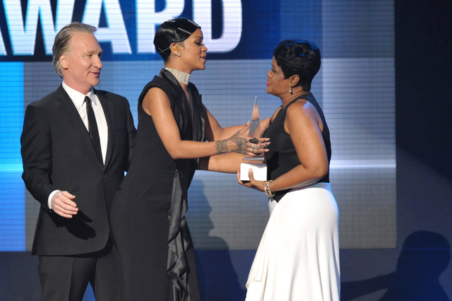 Bill Maher, left, and Rihanna's mother Monica Braithwaite, right, present the Icon award to Rihanna on stage at the American Music Awards at the Nokia Theatre L.A. Live on Sunday, Nov. 24, 2013, i ...