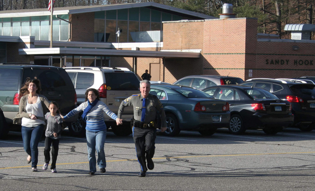 FILE - In this Friday, Dec. 14, 2012, file photo provided by the Newtown Bee, a police officer leads two women and a child from Sandy Hook Elementary School in Newtown, Conn., where a gunman opene ...