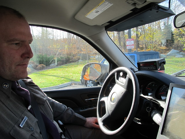 New York State Trooper Clayton Howell checks a screen that displays driving records inside his patrol vehicle in Hawthorne, N.Y., on Thursday, Nov. 14, 2013. Troopers are using a fleet of tall, un ...