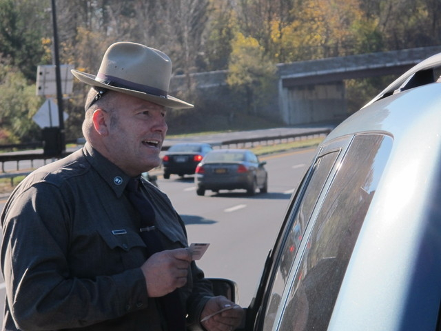 New York State Trooper Clayton Howell checks a driver's license after making a traffic stop for distracted driving in Greenburgh, N.Y., on Thursday, Nov. 14, 2013. Troopers are using a fleet of ta ...