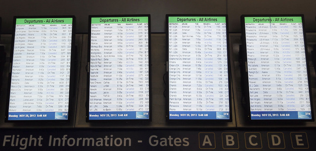 Departure boards display dozens of canceled flights in terminal D at Dallas-Fort Worth International airport on Monday. Nearly 300 American Airlines and American Eagle flights were canceled in and ...