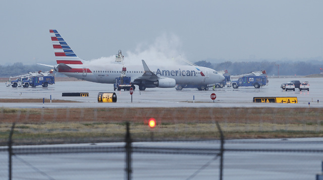 Crews spray deicing solution onto an American Airlines 737 before departure at Dallas-Fort Worth International airport on Monday. Winter weather has caused travel disruptions throughout the area i ...