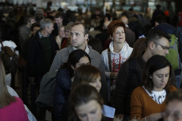 Travelers wait in a winding line to pass through customs and border control at John F. Kennedy Airport in New York on Monday. A winter storm system blamed for at least 10 fatal accidents in the We ...