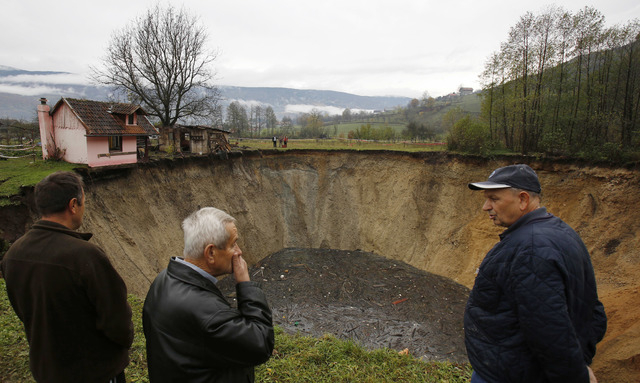 People gather around a huge sinkhole in the village of Sanica, Bosnia, on Nov. 21. Only weeks ago, the spot was a pond full of fish and floating green algae, lined with old willow and plum trees,  ...