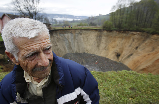 Ekrem Keramovic stands near a huge sinkhole in the village of Sanica, Bosnia, on Nov. 21. Only weeks ago, the spot was a pond, about 20 meters in diameter and about 10 meters deep and full of fish ...