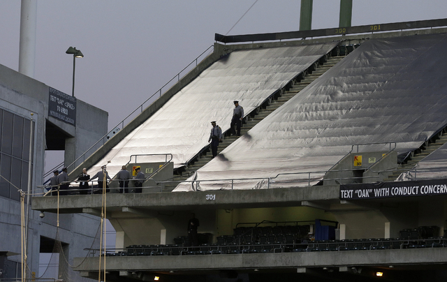 Law enforcement officials walk in the upper deck of O.co Coliseum after an NFL football game between the Oakland Raiders and the Tennessee Titans in Oakland, Calif., Sunday, Nov. 24, 2013. Authori ...