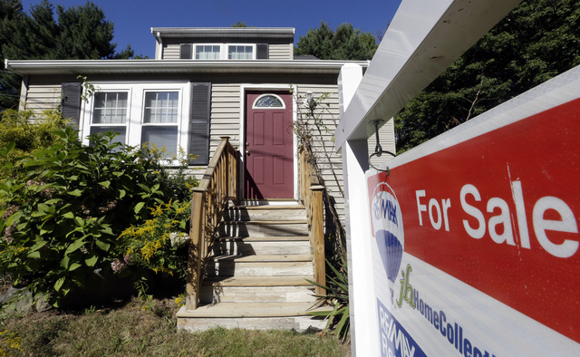 "In this Wednesday, Sept. 18, 2013, file photo, a ""For Sale"" sign hangs in front of a house in Walpole, Mass. Home price gains in Las Vegas slowed in September, a new report indicates. (AP Photo/St ..."