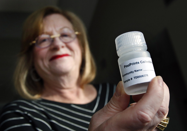 Barbara Kansky, condo manager of Devon Wood in Braintree, Mass., holds up a plastic bottle provided by the Knoxville, Tenn.-based BioPet Vet Lab to ship a small sample of feces. Apartment and cond ...