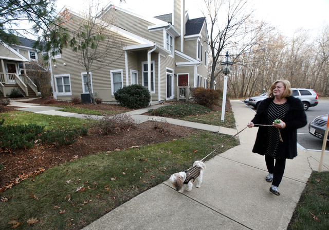 Barbara Kansky, condo manager of Devon Wood in Braintree, Mass., walks her dog, Justine, along a sidewalk on the 350-acre property. Dogged by complaints from those who have experienced the squishy ...