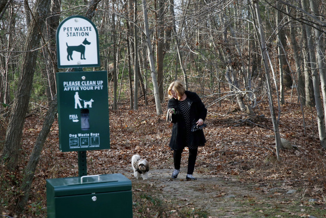 Barbara Kansky, condo manager of Devon Wood in Braintree, Mass., walks her dog, Justine, near one of several doggie waste stations on the 350-acre property. Dogged by complaints from those who hav ...