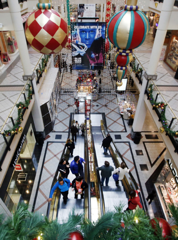 Shoppers ride escalators in a mall in Cambridge, Mass., on Tuesday. Shoppers in many states will line up for deals hours after their Thanksgiving dinners, but stores in Rhode Island, Massachusetts ...