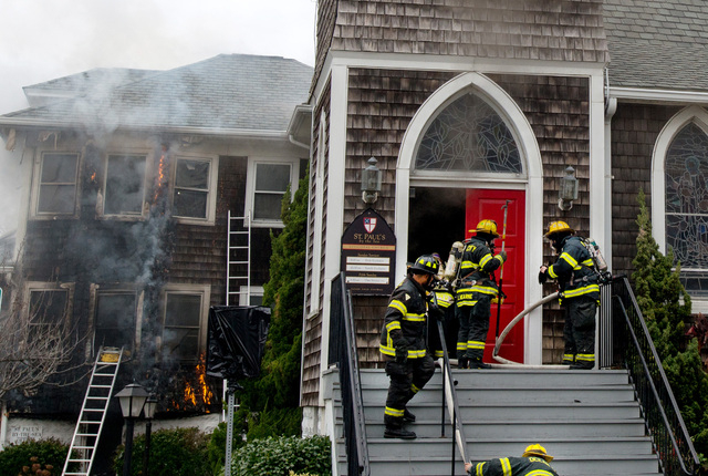 Ocean City firefighters enter St. Paul's By The Sea Episcopal Church as flames roll up the wall of the rectory, in Ocean City, Md., Tuesday, Nov. 26, 2013. Authorities say two people are dead and  ...