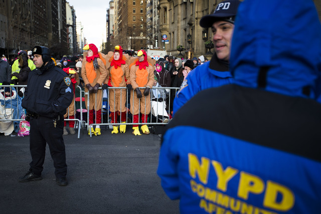 Spectators dressed as turkeys stand behind police barricades as they wait for the 87th Annual Macy's Thanksgiving Day Parade on Thursday. (AP Photo/John Minchillo)
