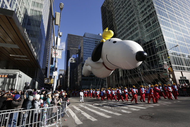 Snoopy flies by as spectators look on during the Macy's Thanksgiving Day Parade on Thursday in New York. After fears the balloons could be grounded if sustained winds exceeded 23 mph, Snoopy, Spid ...