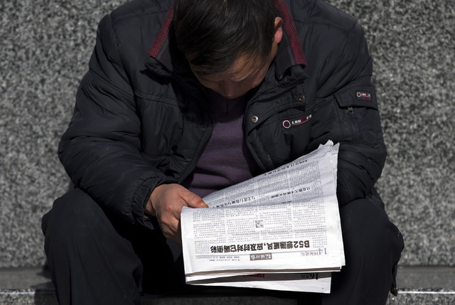 A Chinese man reads a newspaper which reports that U.S., Japan and South Korea sent flights through China's newly declared maritime air defense zone, in Beijing, China Friday, Nov. 29, 2013. China ...