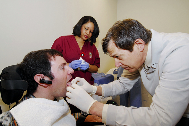 This undated handout photo provided by the Shepherd Center shows Jason DiSanto, left, receiving a tongue piercing at Georgia Tech in Atlanta.  An experimental device is letting paralyzed people dr ...