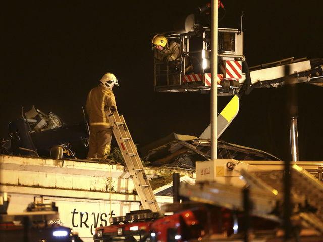 Firefighters inspect the damage at the site of a helicopter crash,  in Glasgow early Saturday Nov. 30, 2013. The police helicopter crashed late Friday night into the roof of a popular pub in Glasg ...