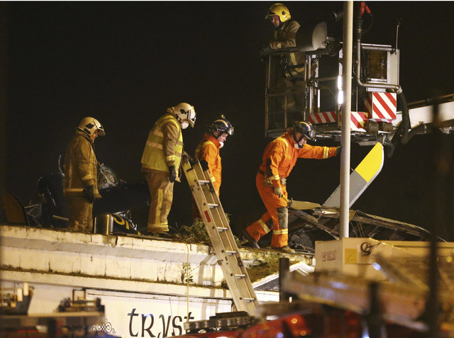 Firefighters and rescue workers inspect the damage at the site of a helicopter crash,  in Glasgow early Saturday Nov. 30, 2013. The police helicopter crashed late Friday night into the roof of a p ...