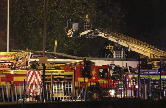 A firefighter inspects the damage at the site of a helicopter crash,  in Glasgow early Saturday Nov. 30, 2013. The police helicopter crashed late Friday night into the roof of a popular pub in Gla ...
