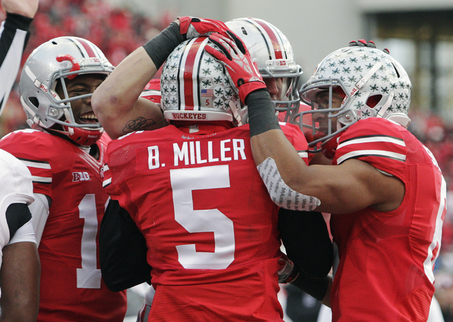 Ohio State quarterback Braxton Miller (5) is congratulated on his touchdown against Indiana during the second quarter of an NCAA college football game, in Columbus, Ohio. (AP Photo/Jay LaPrete, File)