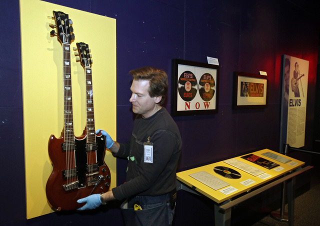 Andre Sepetavec installs a double-necked guitar in the Elvis exhibit at the Rock and Roll Hall of Fame and Museum in Cleveland. (AP Photo/Mark Duncan)