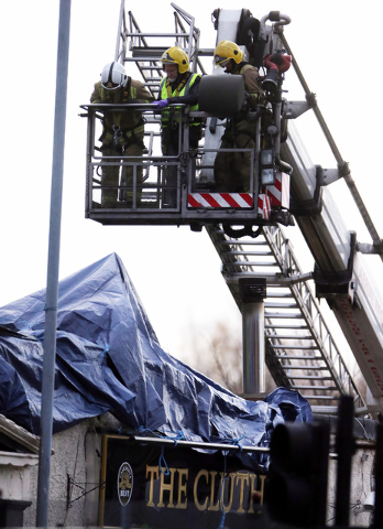 Scottish Fire and Rescue services at the scene Saturday, Nov. 30, 2013, following the helicopter crash at the Clutha Bar in Glasgow, Scotland.  Scottish emergency workers were sifting through wrec ...