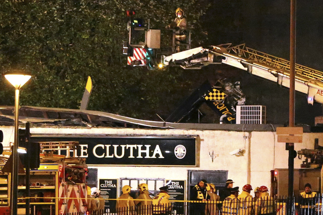 Police officers and firefighters inspect the damage of a helicopter crash, at a pub in Glasgow early Saturday Nov. 30, 2013. The police helicopter crashed late Friday night into the roof of a popu ...