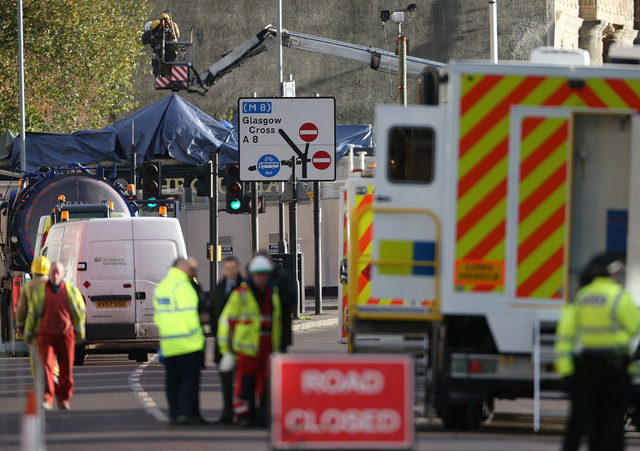Police and Scottish Fire and Rescue services at the scene Saturday, Nov. 30, 2013, following the helicopter crash at the Clutha Bar in Glasgow, Scotland.  Scottish emergency workers were sifting t ...