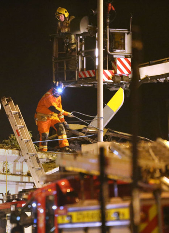 A firefighter and a rescue worker inspect the damage on the building, at the site of a helicopter crash,  in Glasgow early Saturday Nov. 30, 2013. The police helicopter crashed late Friday night i ...